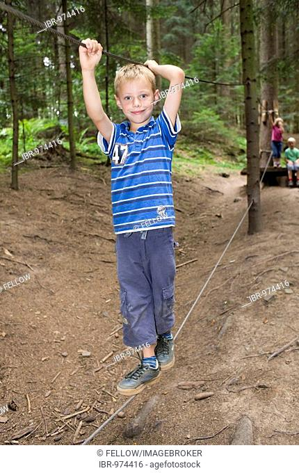 6-year-old boy balancing on a rope in a forest