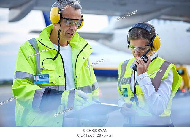 Air traffic control ground crew workers with clipboard talking on airport tarmac