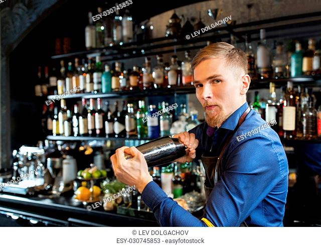 alcohol drinks, people and luxury concept - barman with shaker preparing cocktail at bar