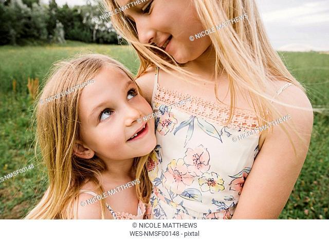 Two little sisters cuddling on a meadow