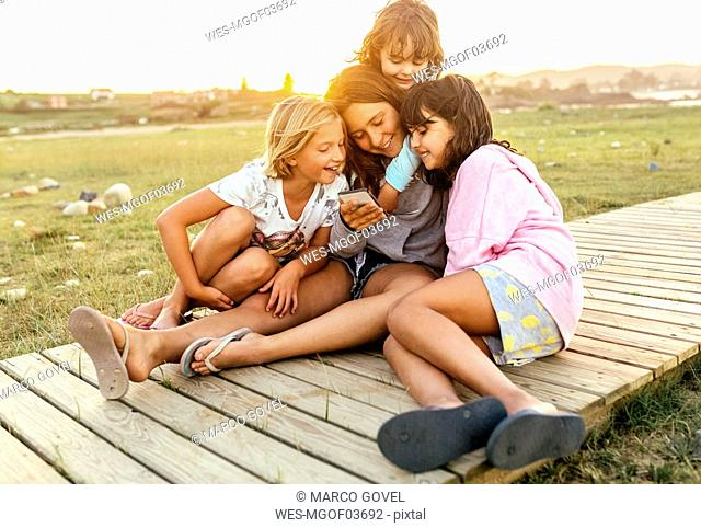 Four girls sitting together on boardwalk looking at cell phone