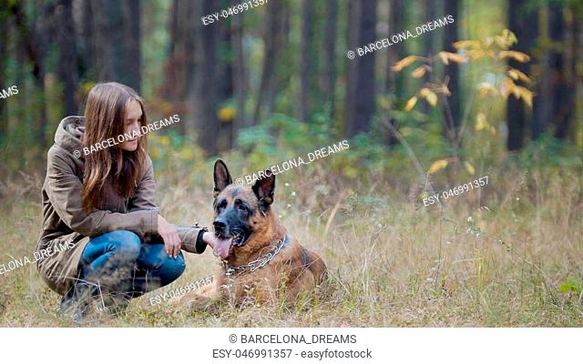 Young woman in autumn park with her pet - german shepherd, telephoto