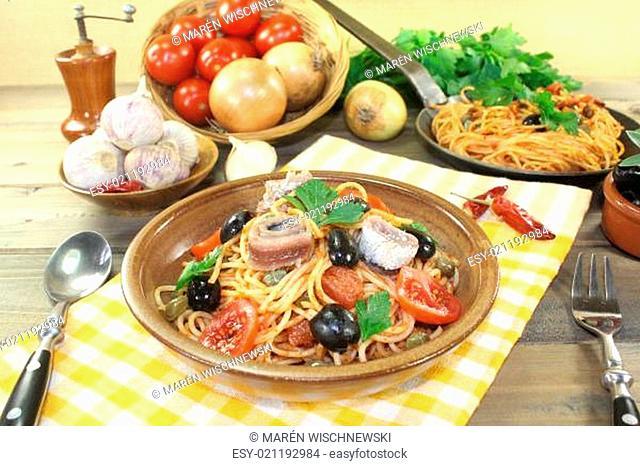 spaghetti alla puttanesca with capers and tomatoes on a napkin