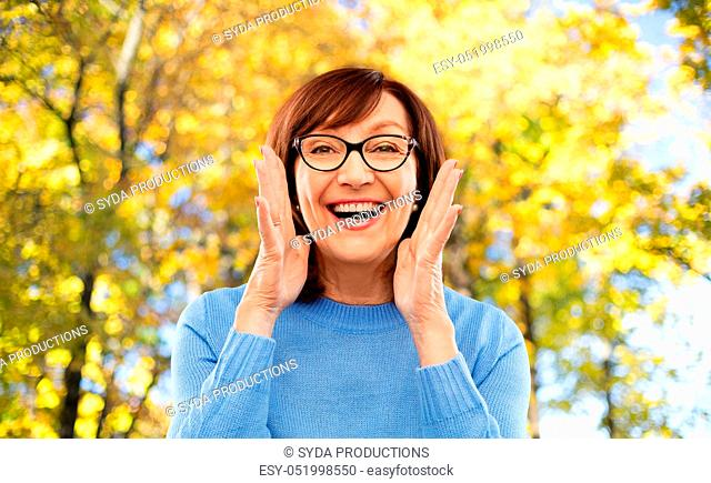senior woman in glasses calling over autumn park