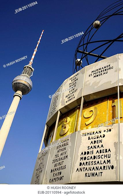 Weltzeituhr also known as the World Clock in Alexanderplatz with the Fernsehturm Berlins TV Tower in the background