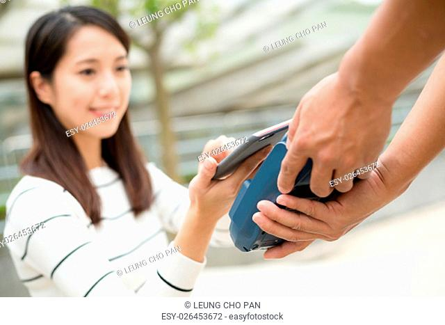 Young Woman pay with cellphone by NFC