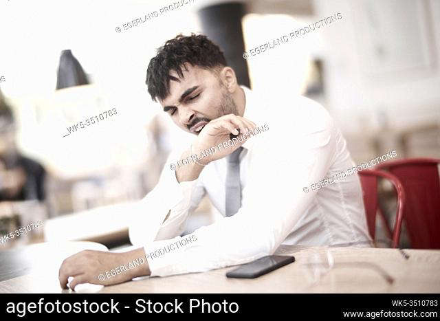 Businessman in cafe, yawning