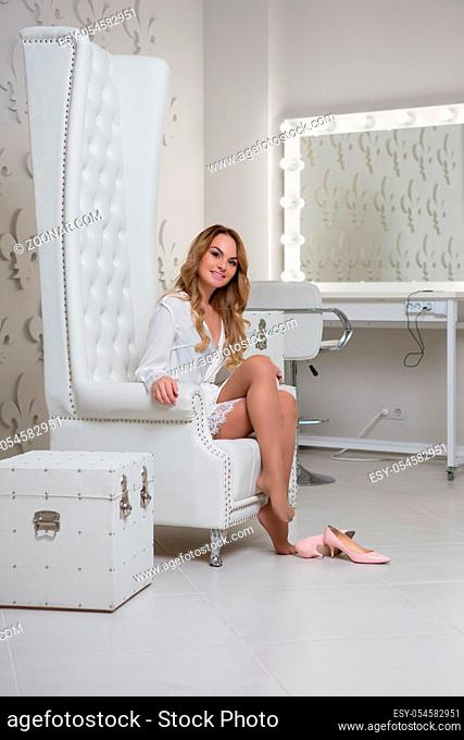 Beautiful lady posing in studio sitting in a chair and wearing a white bathrobe