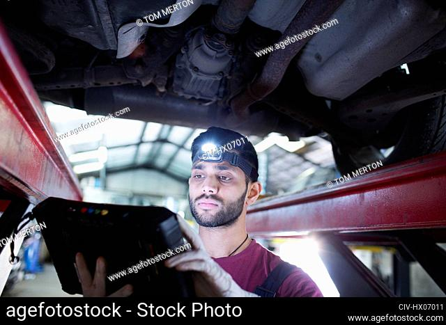 Male mechanic with headlight and diagnostic equipment working under car in auto repair shop