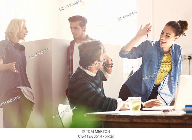 Creative young business people high fiving in office