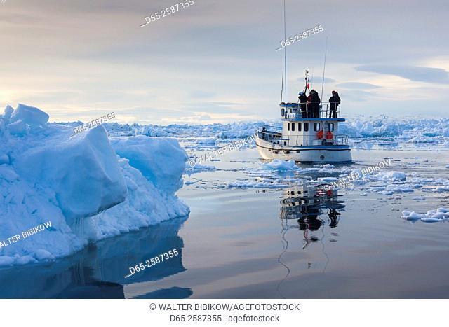Greenland, Disko Bay, Ilulissat, fishing boat in floating ice at sunset