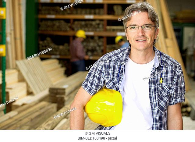 Hispanic carpenter holding hard hat
