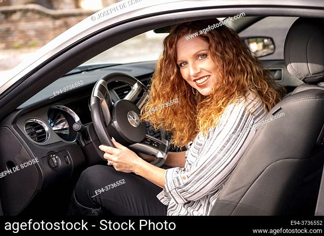 A beautiful 41 year old redheaded woman in the driver's seat of a car