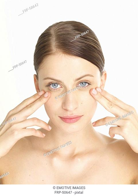 Woman is massaging her face under her eyes