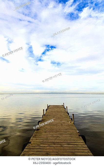 Wooden jetty perspective and big sky onto lake without people