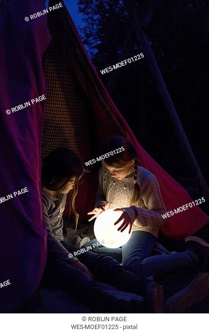 Two girls sitting in tipi, holding lamp as moon