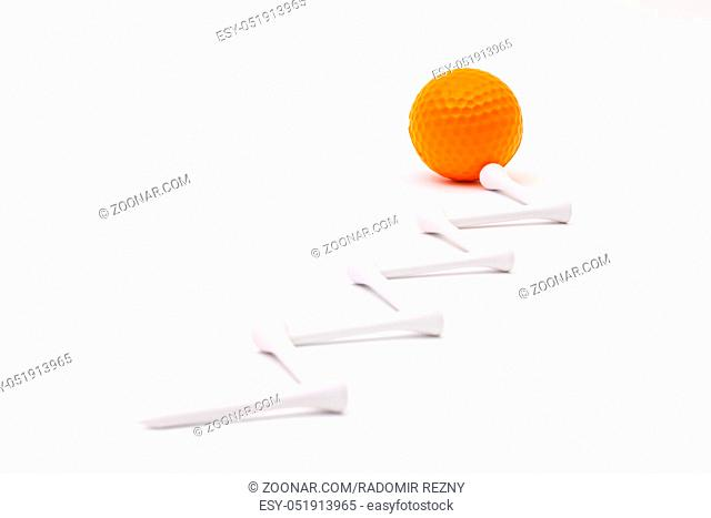 White golf balls and wooden tees on the white background.Golf concept