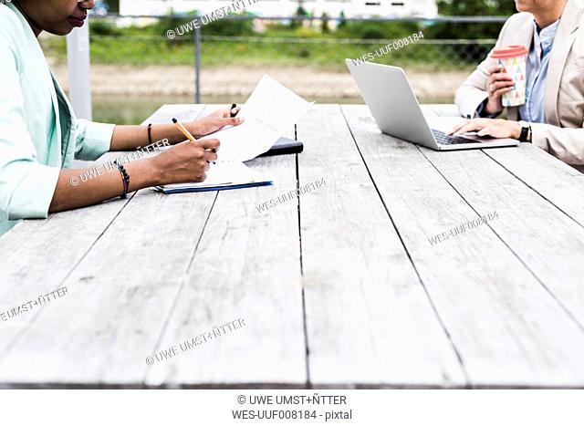 Two businesswomen working on terrace