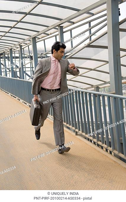 Businessman checking the time while running on a footbridge, Gurgaon, Haryana, India