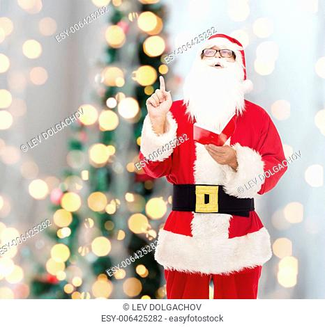 christmas, holidays, gesture and people concept - man in costume of santa claus with notepad pointing finger up over tree lights background