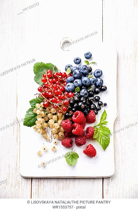 Mix of fresh berries with leaves on rustic wooden background