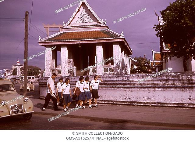 Candid photograph of Thai students in school uniforms, walking on a sidewalk near traffic and pitched-roof buildings, Bangkok, Thailand, 1964