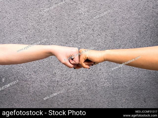 Arms of two young women fist bumping against gray background