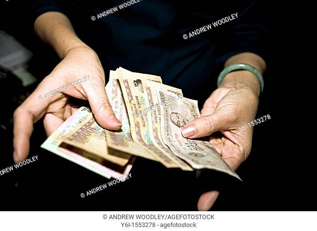 Cashier counts money store Hoi An Vietnam