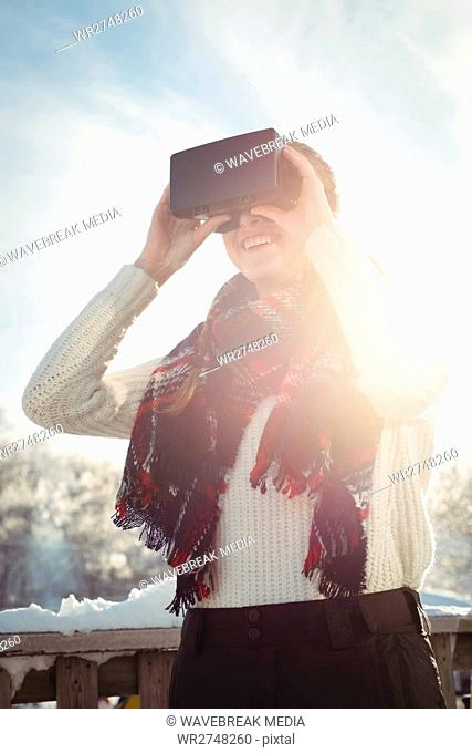 Woman in winter wear using VR headset