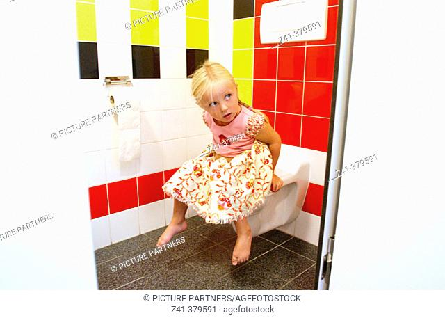 Child sits on toilet