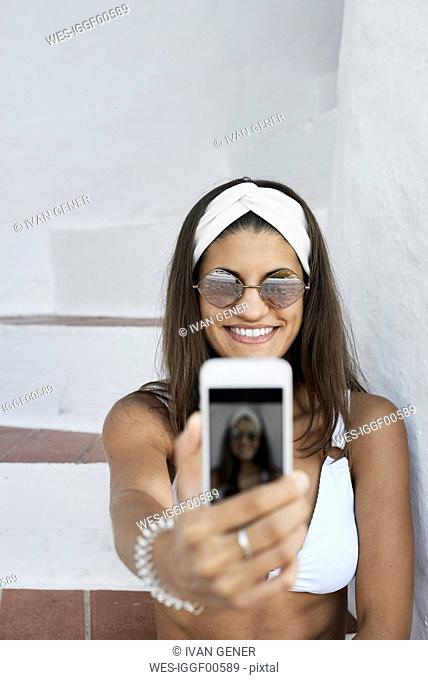 Portrait of smiling young woman wearing white bikini taking selfie with smartphone