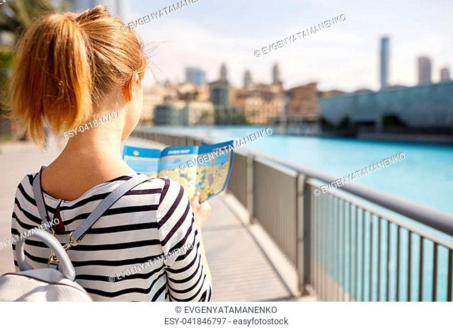 girl tourist travels with a map through streets of city