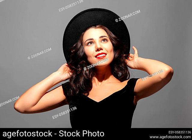 Profile portrait of a beautiful elegant brunette smiling lady woman with long hair wearing a black hat and looks up