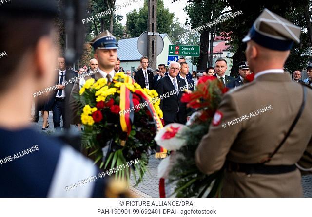 01 September 2019, Poland, Wielun: Federal President Frank-Walter Steinmeier (M) and Polish President Andrzej Duda lay down flower arrangements at the memorial...