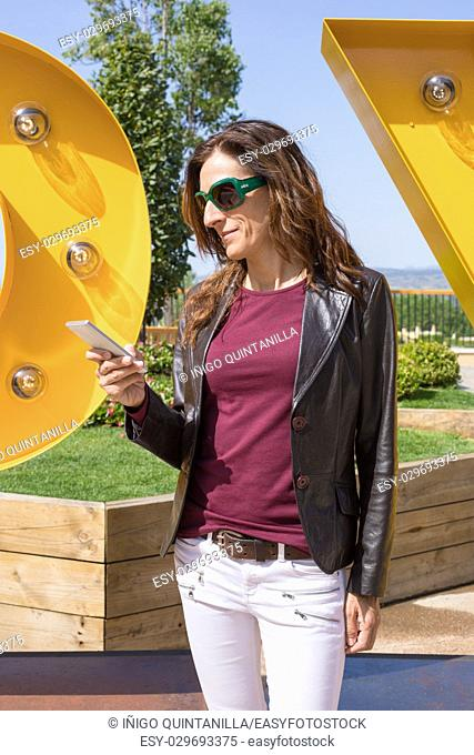 brown hair woman with white jeans, red shirt, leather blazer jacket and sunglasses, standing in urban park, looking and typing on mobile smart phone