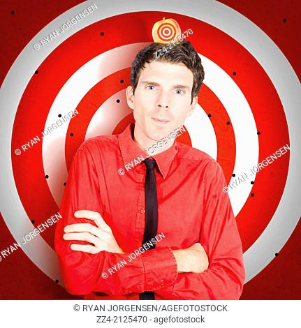 Business man standing in focus in front of a target sign with apple on head. William tell concept