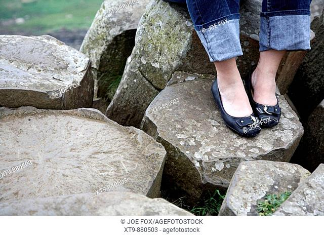 womans legs wearing jeans and shoes sitting on red basalt hexagonal rock formations at the giants causeway county antrim northern ireland uk