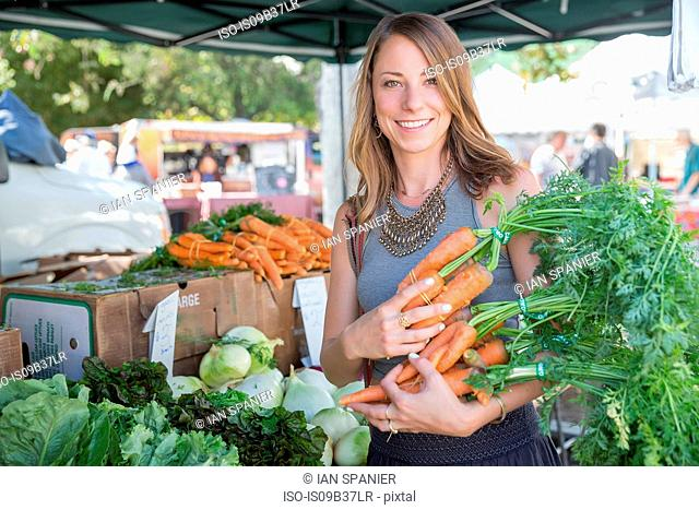 Woman at fruit and vegetable stall holding carrots