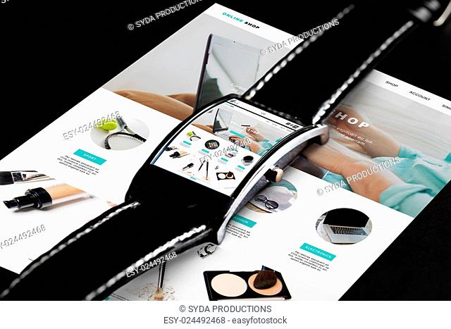 modern technology, internet shopping, object and media concept - close up of black smart watch with online shop web page on screen