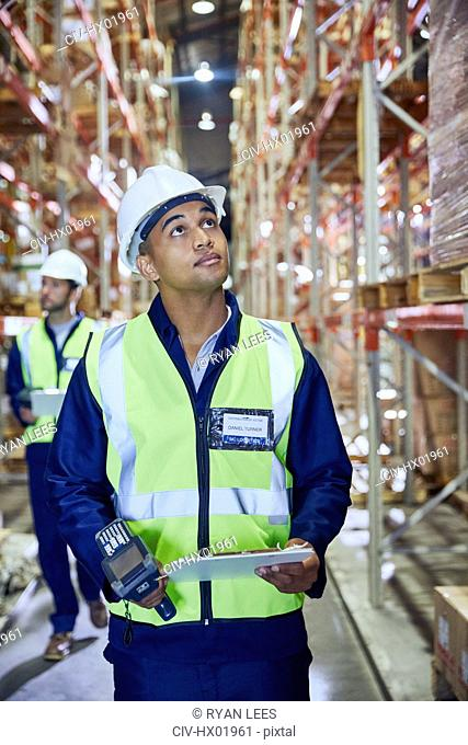 Worker with clipboard and scanner looking up in distribution warehouse