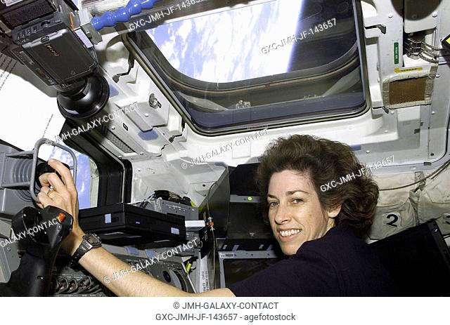 Mission Specialist (MS) Ellen Ochoa works at the Remote Manipulator System (RMS) controls on the aft flight deck of Atlantis, Orbiter Vehicle (OV) 104