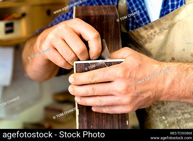 Guitar maker in his workshop, close-up