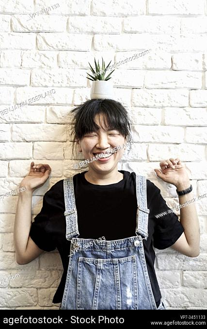 Korean woman holding a cup with leaves on her head