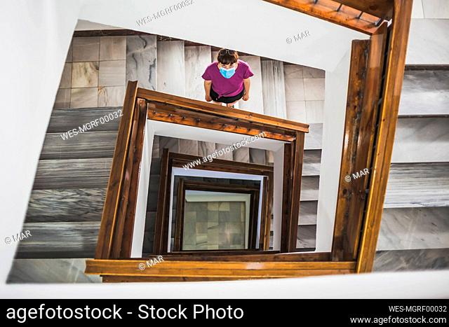 Young woman wearing face mask looking up while standing on spiral staircase