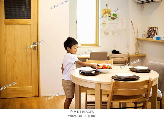 Family home. A boy setting the table for a meal