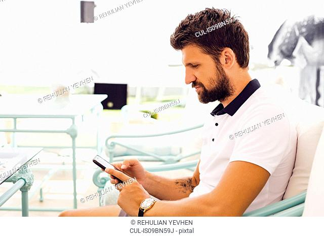Man texting on terrace chair