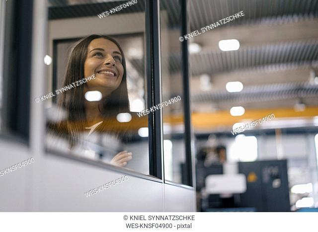 Confident woman working in high tech enterprise, looking out of control room