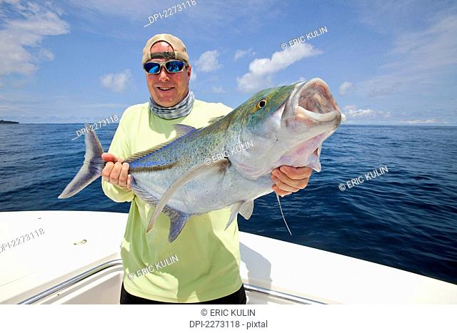 Man holds fresh caught jack fish, panama