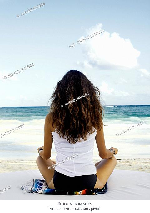 Young woman meditation on beach, rear view
