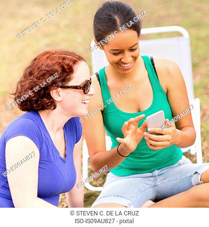 Young woman sitting crossed legs using smartphone, looking down smiling